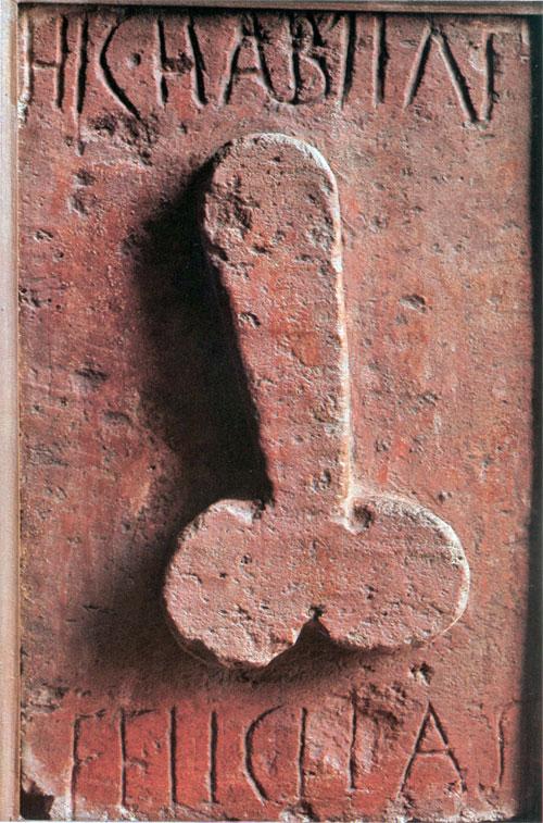 """HIC HABITAT FELICITAS (""""A felicidade mora aqui""""). Essa frase com a ilustração foi colocada originalmente no centro do arco sobre o forno de um padeiro de Pompeia para espantar os maus espíritos. No começo do século XX, a placa foi transferida, juntamente com dúzias de artefatos que hoje em dia dificilmente seriam considerados ofensivos, para o """"Gabinete de Objetos Obscenos"""" do Museu Arqueológico de Nápoles. A mesma inscrição, seguida de nil intret mali (""""Que nenhum mal entre""""), mas sem a ilustração, foi encontrada em um mosaico na entrada de uma casa de Salisburgo. Restaram muitos anéis decorados com um símbolo fálico daquela época, que eram usados por crianças como amuletos de proteção."""